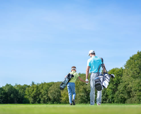 adult and child golfing